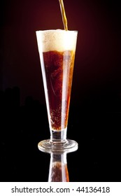 Dark Red Foaming Beer Being Poured into a Pilsner Glass.