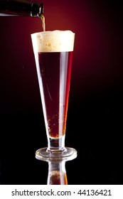 Dark Red Foaming Beer Being Poured into a Pilsner Glass from a Bottle.