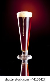 Dark Red Foaming Beer Dripping Over the Edge of a Pilsner Glass.