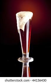 Dark Red Foaming Beer Overflowing from the Edge of a Pilsner Glass.