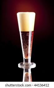 Dark Red Foaming Beer in a Pilsner Glass.