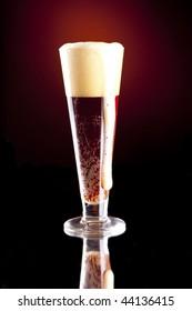 Dark Red Foaming Beer in a Pilsner Glass Overflowing.