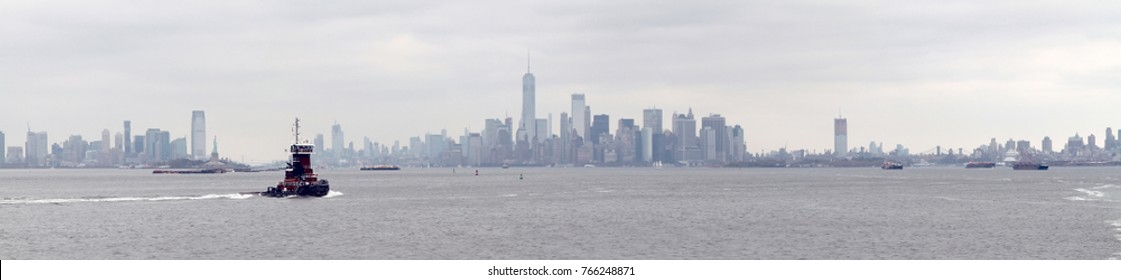 Dark red harbour launch crossing Hudson River against grey foggy cityscape. New York. USA.