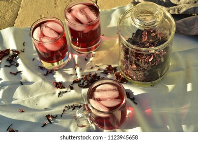 dark red Hibiscus flower petal tea with ice aka Fleur de Jamaica in Mexico used to make Aguas Frescas or sweet and natural cold drinks