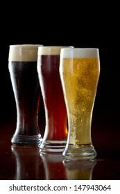 dark, red and light beer served on a dark bar