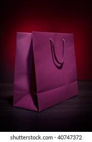 Dark red paper bag on dark table top
