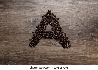 Dark roasted coffee bean arranged on a wooden table in the shape of text alphabet letter A