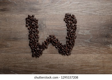 Dark roasted coffee bean arranged on a wooden table in the shape of text alphabet letter W