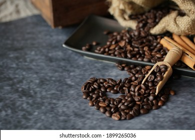Dark roasted coffee bean with wooden spoon and assorted sugar and cream with bakery preparation for cafe or coffee shop. Heart coffee in love for Valentine's day