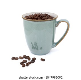 Dark roasted coffee beans in green mug and spilled beside, on a white background