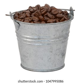 Dark roasted coffee beans in a miniature metal bucket, isolated on a white background