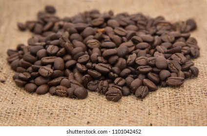 Dark roasted coffee beans on a woen hessian cloth