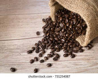 Dark roasted Coffee beans in sackcloth bag on wood background