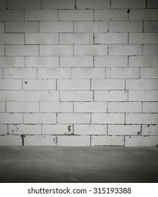 Dark room with cement floor and block wall background