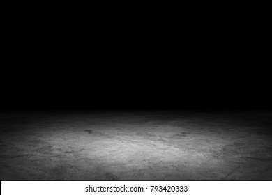 Dark room with concrete floors and spotlights.