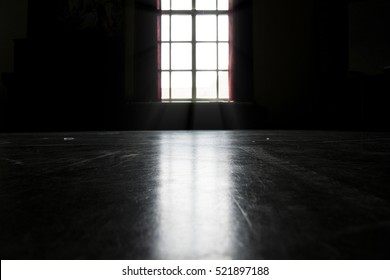 Dark room illuminated by bright light shining trough a window