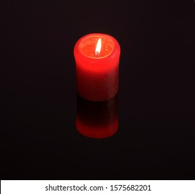 In a dark room lit candle burns