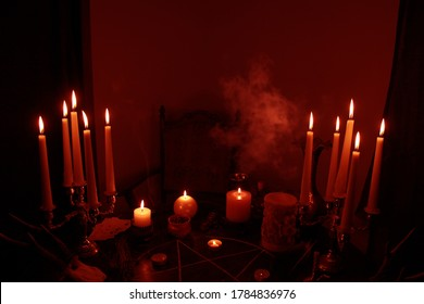 in a dark room on a round esoteric table candles burn, smoke, animal skulls lie, a pentagram is drawn, a red heart model, candles, a concept of magic, witchcraft