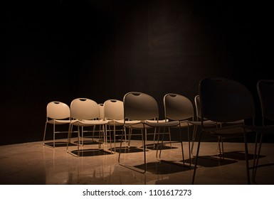 Dark room seats chairs auditorium black walls and spotlight white chair in row