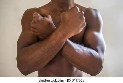 Dark rown skin black African American man with hands across chest
