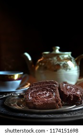 A dark, rustic and creatively lit concept image for the very traditional English afternoon tea with slices of festive chocolate sponge yule log. Generous accommodation for copy space.