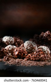 Dark, rustic and creatively lit festive liquer chocolates with cocunut and crushed nuts with generous accommodation for copy space. The perfect image for your Christmas dessert menu cover art.