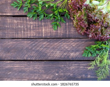 Dark rustic wooden background, free space for text. Frame of salad leaves, fresh greenery. Ingredients for healthy cooking, salad making. Vegetarian food concept. Top view. Copy space