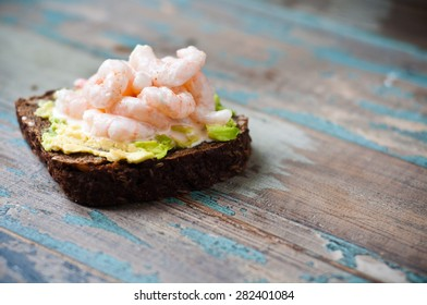 Dark rye bread open sandwich topped with fresh prawns or shrimps on avocado. A healthy snack inspired by Scandinavian cuisine and served on a rustic wooden tray.