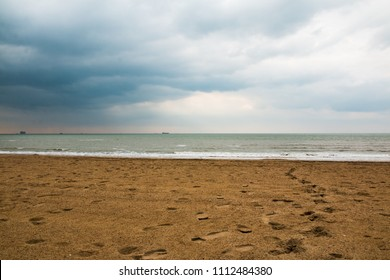 Dark sands with many footprints on the beach under low cloudy sky in a day
