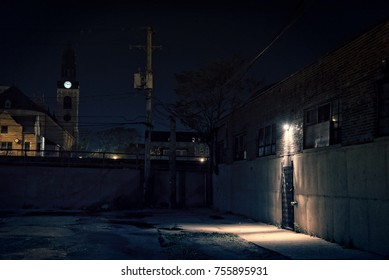 Dark scary alley at night with warehouse entrance, gated door and church tower in background.