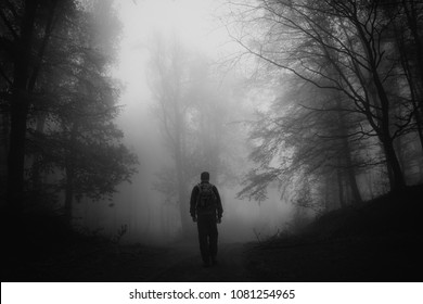 dark scary forest scene with man silhouette on dark road