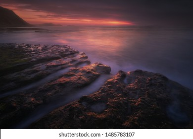 dark seascape in the coast with rocks at dusk