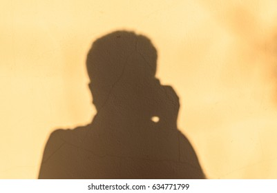 Dark shadow man in the house wall, brown wall background