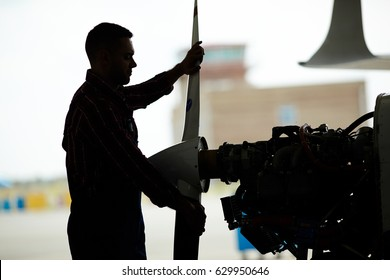 Dark silhouette of aircraft engineer dismantling jet plane in hangar, taking of propeller part and checking turbines