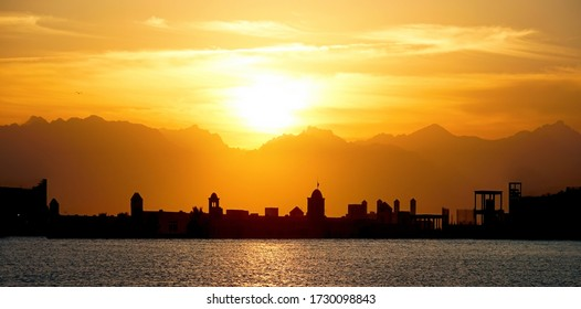 Dark silhouette of Eastern city against the background of mountains at sunset. Beautiful panorama in orange tones.