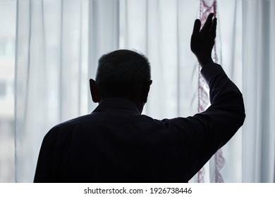 Dark silhouette of elderly man waving with hand goodbye gesture through window rear view.