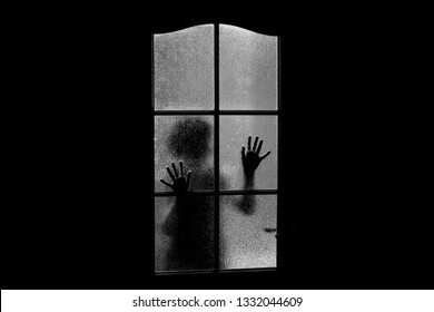 Dark silhouette of girl behind glass. Locked alone in room behind door on Halloween in grayscale. Nightmare of child with aliens, monsters and ghosts. Evil in home in monochrome. Inside haunted house.