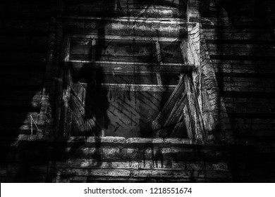 Dark silhouette of a girl and an old wooden house (black and white photo, double exposure)