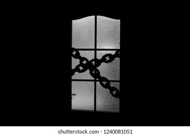 Dark silhouette of glass door with chain. Locked on chain alone in room behind door on Halloween. Evil in home. Inside haunted house in monochrome. Alone in dark. Night kidnapping in grayscale.