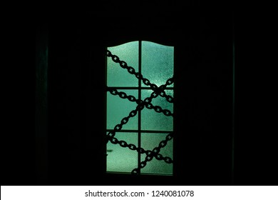 Dark silhouette of glass door with chain in supernatural green light. Locked on chain alone in room behind door on Halloween. Night kidnapping. Evil in home. Inside haunted house. Alone in dark.