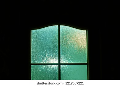 Dark silhouette of glass door in supernatural green light. Locked alone in room behind door on Halloween. Nightmare with aliens, monsters and ghosts. Evil in home. Inside haunted house. Alone in dark.
