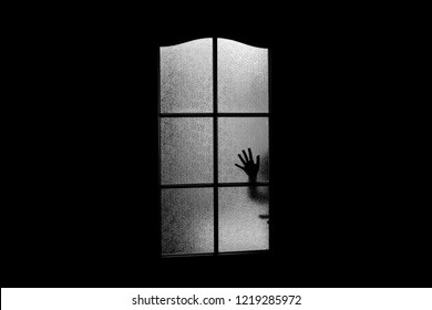 Dark silhouette of hand behind glass in supernatural light. Locked alone in room behind door on Halloween. Nightmare of kid with aliens, monsters and ghosts. Evil in home. Сhild inside haunted house.