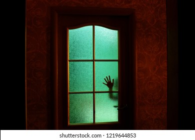 Dark silhouette of hand behind glass in supernatural green light. Locked alone in room behind door on Halloween. Nightmare of child with aliens, monsters and ghosts. Evil in home. Inside haunted house
