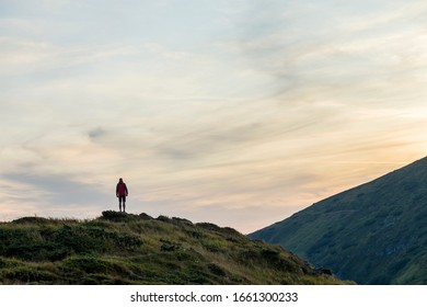 Dark silhouette of a hiker on a mountain at sunset standing on summit like a winner.