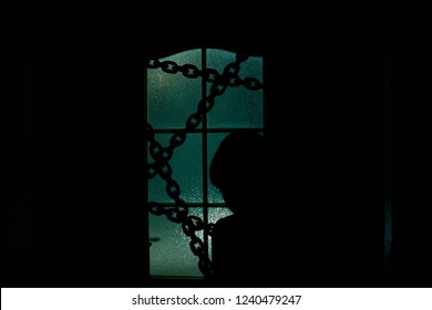 Dark silhouette of kid behind glass door with chain in supernatural green light. Locked alone in room behind door on chain on Halloween. Night kidnapping. Evil in home. Inside haunted house.