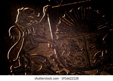 Dark Silhouette of Latvian Coat of Arms heraldry on surface of bronze color euro coin obverse. Shallow depth of field macro photography.