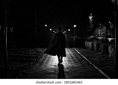 dark silhouette of a male detective in a coat and hat in the rain on a night street in the style of Noir