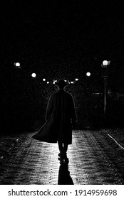 dark silhouette of a man in a coat and hat in the rain on a night street in the city in the style of Noir - Shutterstock ID 1914959698
