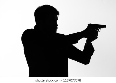 dark silhouette of a man with a gun on a light background