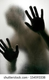 Dark Silhouette of a man with hands on a frosted glass